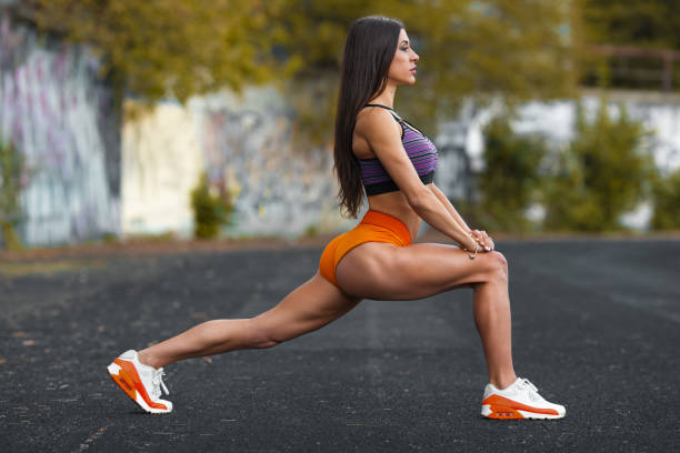 Fitness woman doing lunges exercises for leg muscle workout training, outdoors. Active girl doing front forward one leg step lunge exercise stock photo