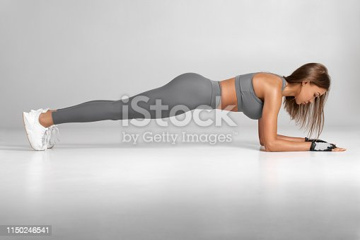 istock Fitness woman doing planking exercise, workout. Slim athletic girl training, isolated on the gray background 1150246541