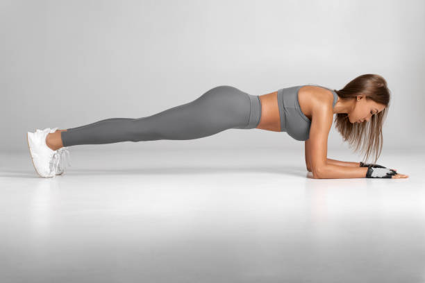 Fitness woman doing planking exercise, workout. Slim athletic girl training, isolated on the gray background stock photo
