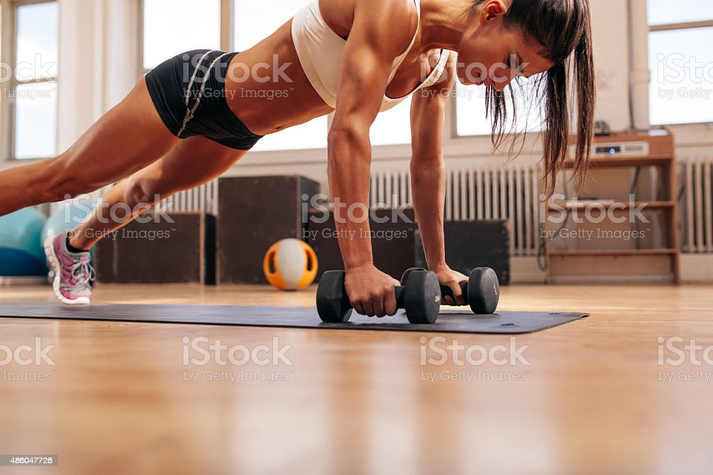 Fitness woman doing push ups exercise with dumbbells stock photo