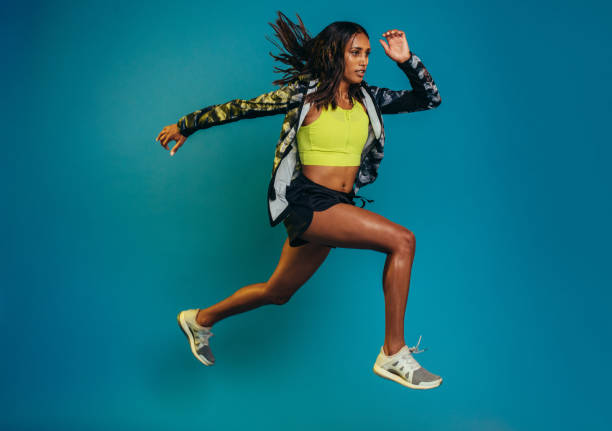 Fitness woman doing running exercise Full length shot of fitness woman running over blue background. Hispanic female model doing running exercise. women's track stock pictures, royalty-free photos & images