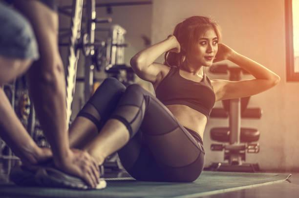 fitness vrouw doet sit-ups oefeningen. vrouw doet abs workout met personal trainer - personal trainer stockfoto's en -beelden