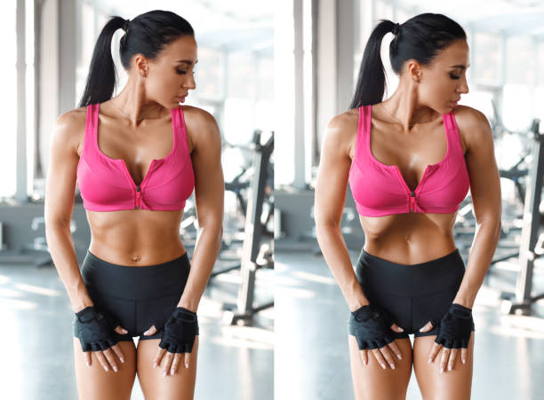 Fitness woman doing stomach vacuum for flat belly in gym. Beautiful athletic girl with slim waist, shaped abdominal stock photo