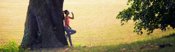 Fitness woman drinking water after workout in the nature stock photo