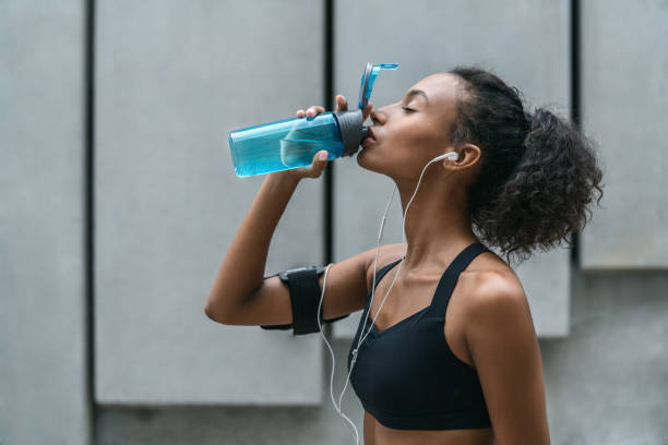 Fitness woman drinking water from a bottle after workout standing by a grey wall Adult, Adults Only, African Ethnicity, Afro, Drinking race distance stock pictures, royalty-free photos & images