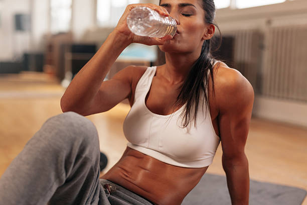 Fitness woman drinking water from bottle at gym stock photo