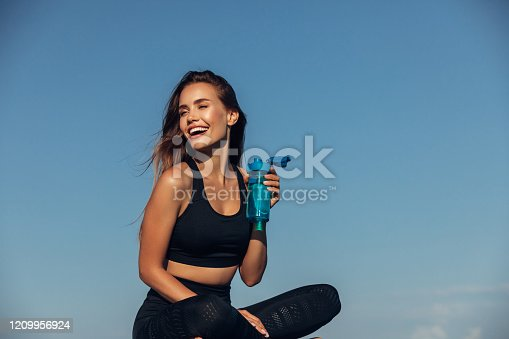 Fitness woman drinks water in front of sea background