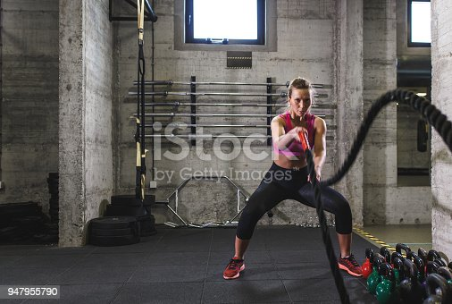 istock Fitness woman exercise in the gym with battle rope. 947955790