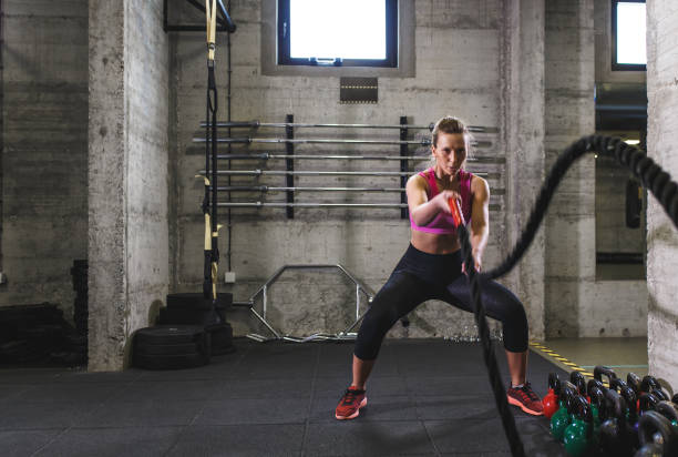 Mujer fitness hacer ejercicio en el gimnasio con la cuerda de la batalla. - foto de stock