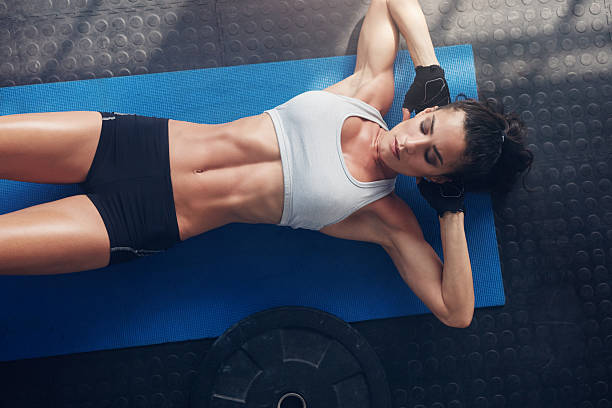 Fitness woman exercising on yoga mat Top view of woman exercising on yoga mat. Fitness female lying on exercise mat with her hands behind head at gym. abdominal muscle stock pictures, royalty-free photos & images