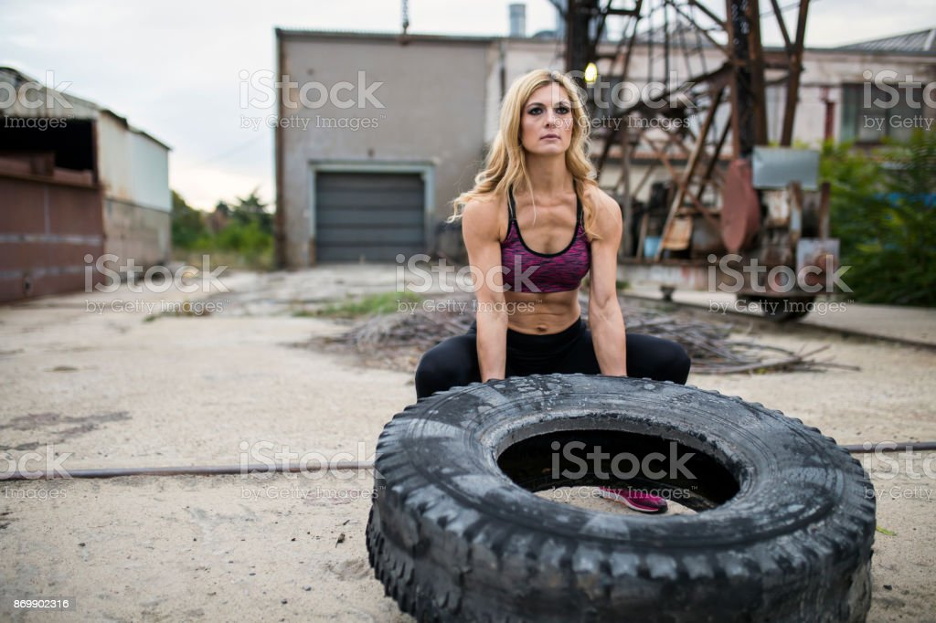 Fitness woman exercising with a truck tire outdoor stock photo