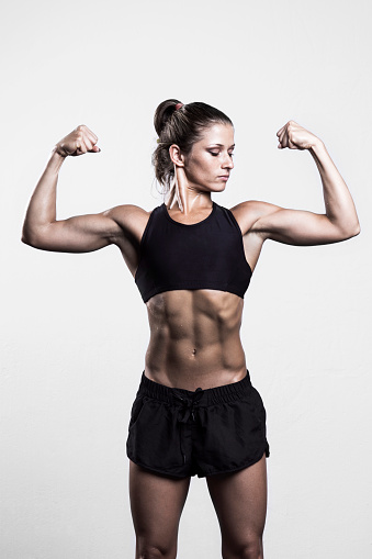 509796496 istock photo Fitness woman flexing muscles 506011536