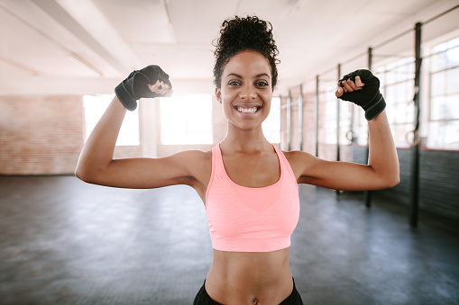 istock Fitness woman flexing muscles 639606608