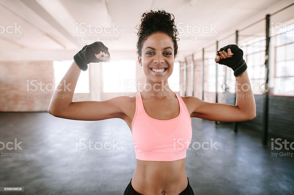 Fitness woman flexing muscles stock photo