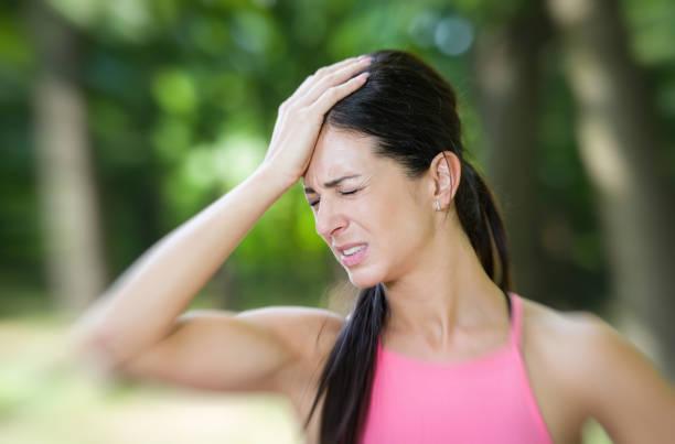 fitness vrouw hoofdpijn in een park - atlete stockfoto's en -beelden