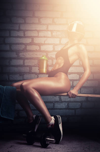 Fitness woman in athletic swimsuit drinking protein shake while workout in indoor gym stock photo