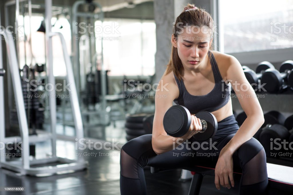 Fitness woman in sport wear pumping up muscules with dumbbells on...