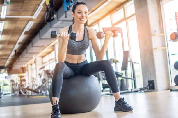 Fitness-Frau in Sportbekleidung Workout mit Hanteln im Sitzen auf Schweizer Ball im Fitnessstudio – Foto
