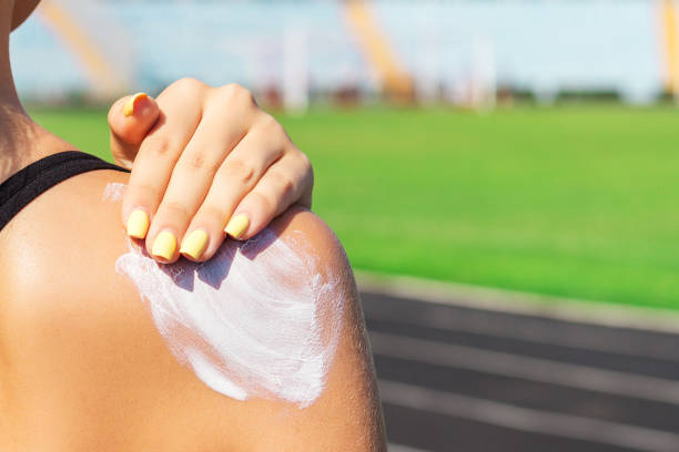 Fitness woman is applying sunscreen on her shoulder before training at the stadium. Protect your skin during sport activity stock photo