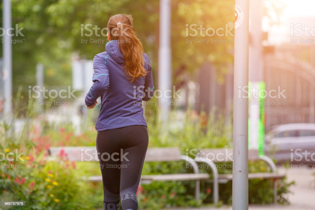 Fitness woman jogging in park in the sunny morning - Royalty-free Adult Stock Photo