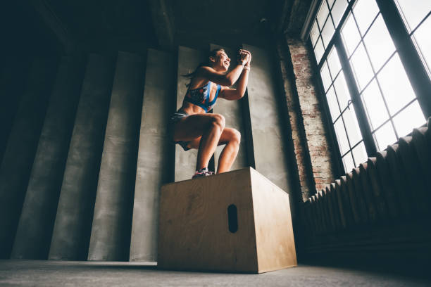 Fitness woman jumping on box. stock photo