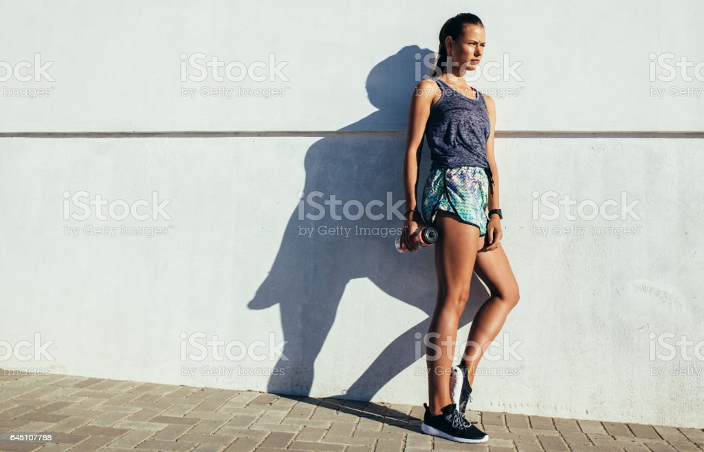Fitness woman leaning to a wall and looking away stock photo