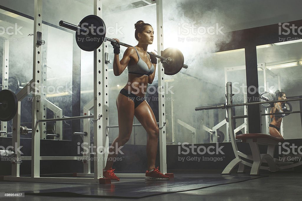 fitness woman lifting weight in gym stock photo