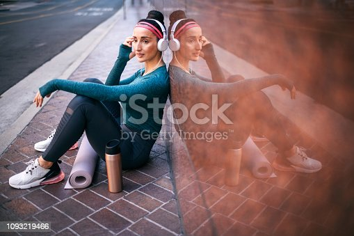 1091470492 istock photo Fitness woman listening to music while sitting with her back against a marble building wall on a street sidewalk downtown 1093219466