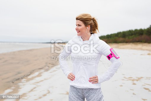 Fitness woman on the beach in winter, middle- aged Caucasian ethnicity woman ready for workout outdoors in wintertime