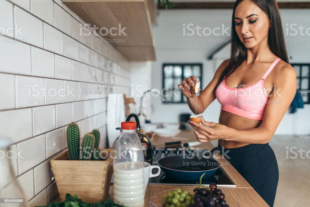 Fitness woman prepare breakfast. Healthy homemade oatmeal with vegetables stock photo