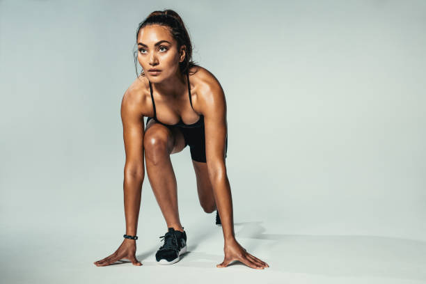 Fitness woman ready for competition Beautiful young woman standing in start position over grey background. Young woman about to start a run. women's track stock pictures, royalty-free photos & images