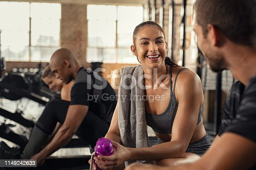 Young woman in conversation with man in gym after workout training. Smiling sweaty girl with towel and water bottle taking break after workout exercise. Exhausted and smiling people in cross training gym talking to each others while sitting on rowing machine.