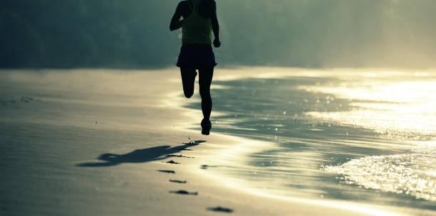Fitness-Läuferin läuft am Sonnenaufgangsstrand – Foto