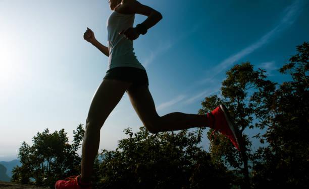 Fitness woman runner running on sunrise mountain top edge stock photo