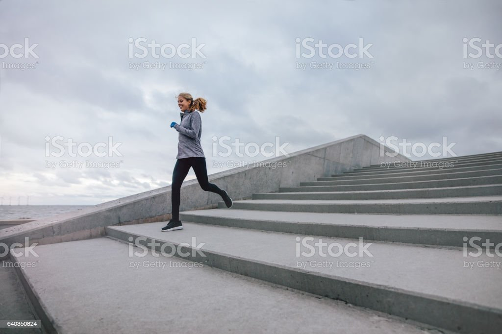 Fitness woman running down on steps stock photo