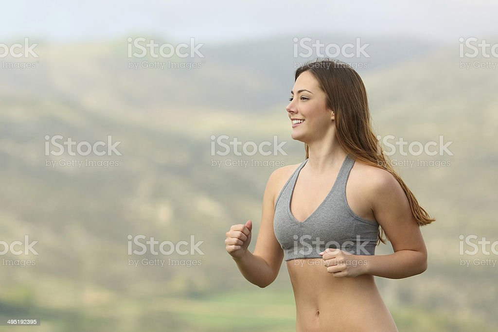 Fitness woman running in the mountain stock photo