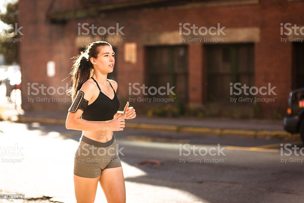 Fitness Woman running on the city against the wall stock photo