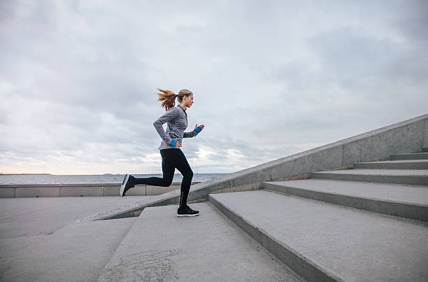 Fitness woman running up on steps - foto de stock