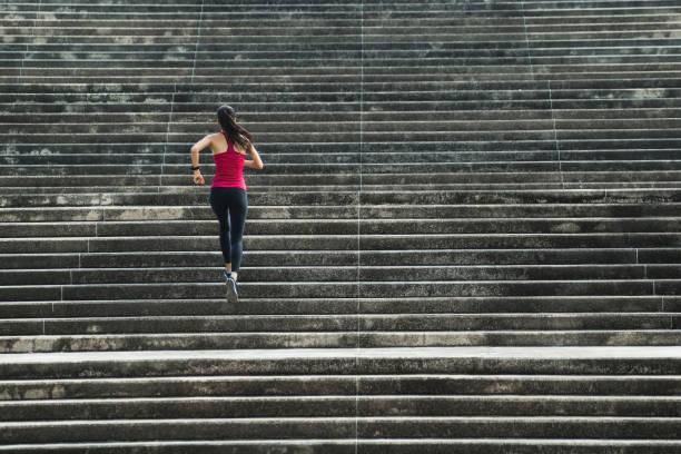 フィットネス女性彼女は階段を実行しています。 - ステップ ストックフォトと画像