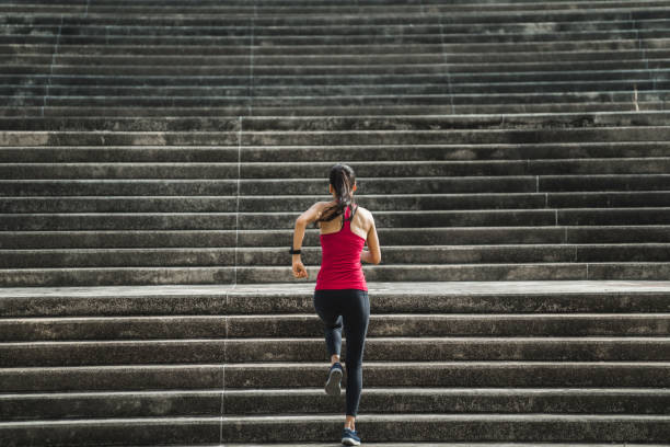 Fitness woman she is running up the stairs. stock photo