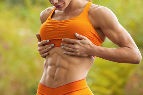 Fitness woman showing abs and flat belly. Athletic girl outdoors, shaped abdominal, slim waist stock photo