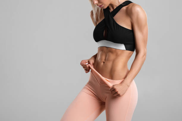 Fitness woman showing abs and flat belly, isolated. Athletic girl shaped abdominal stock photo