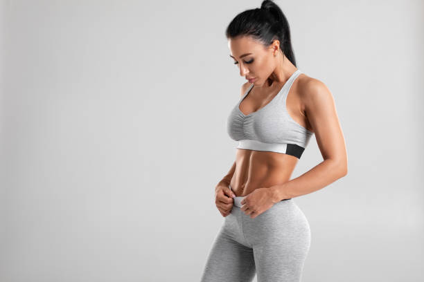 Fitness woman showing abs and flat belly, isolated on gray background. Beautiful athletic girl, shaped abdominal stock photo