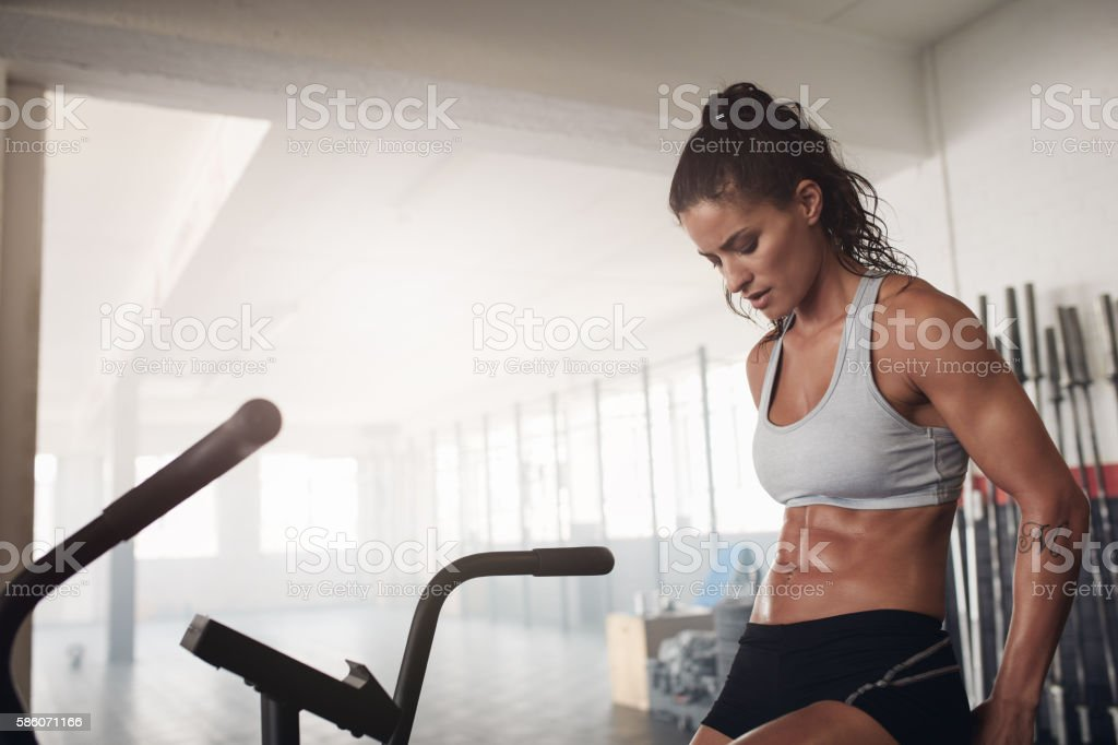 Fitness woman sitting on gym bicycle doing and thinking stock photo