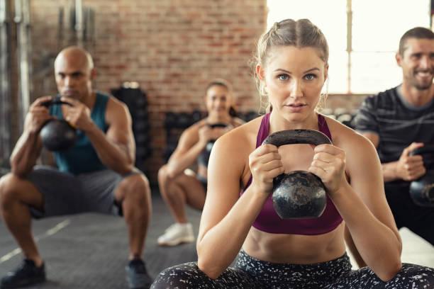 健身婦女蹲在水壺鈴鐺 - 健康的生活方式 個照片及圖片檔