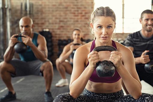 Fitness Woman Squatting With Kettle Bell - zdjęcia stockowe i więcej obrazów 20-29 lat