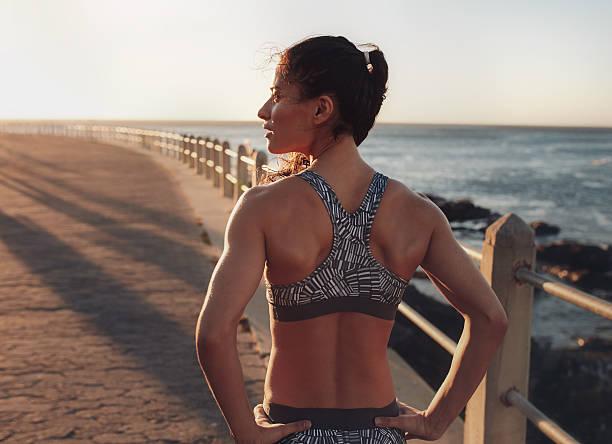 bonne forme femme debout sur une promenade en bord de mer - brassière de sport photos et images de collection
