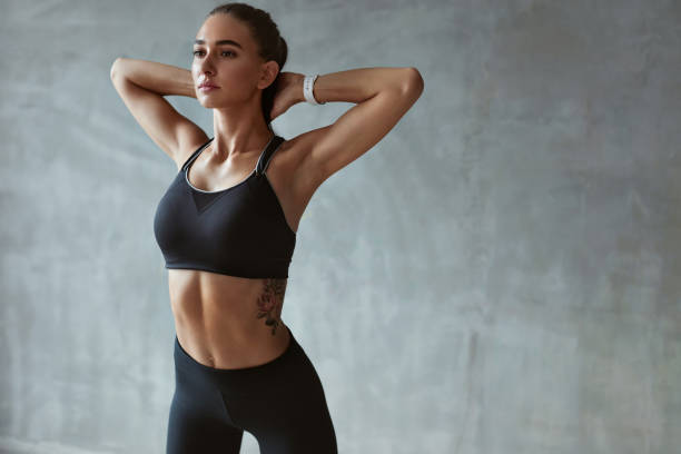 fitness woman stretching arms in stylish black sport clothes - sportsmenka zdjęcia i obrazy z banku zdjęć