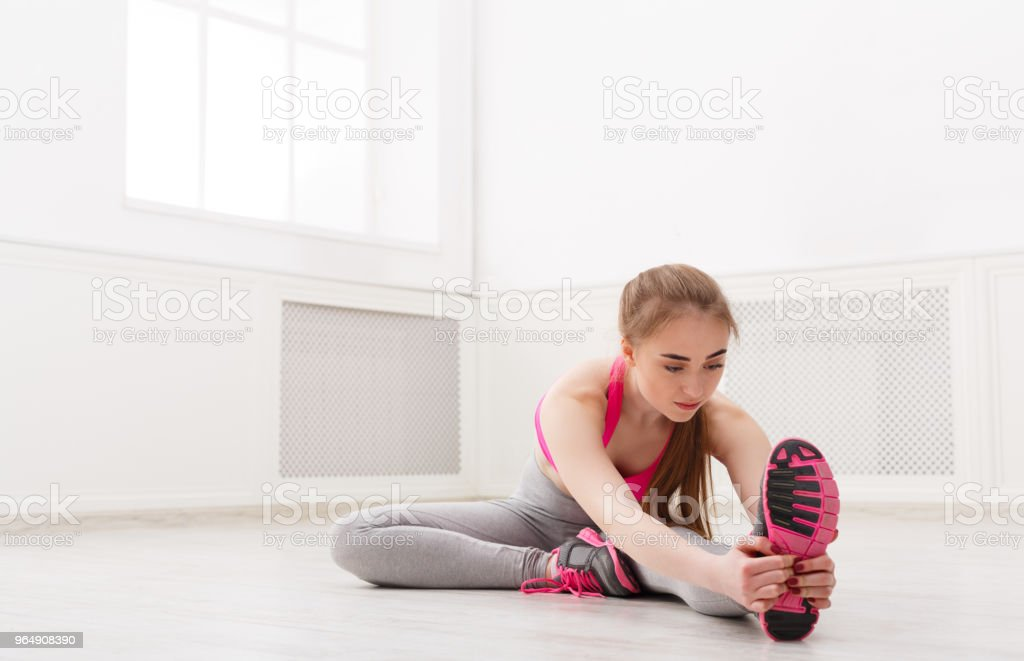 Fitness woman stretching at white background indoors - Royalty-free Adult Stock Photo