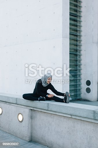 istock Fitness woman stretching her legs. 999805632